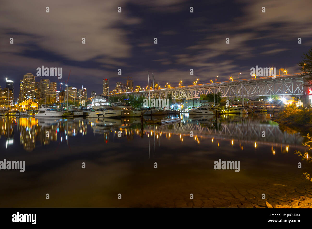 Long Exposure Night Photo of Granville Island Market and Granville Bridge from False Creek Seawall in Vancouver Stock Photo