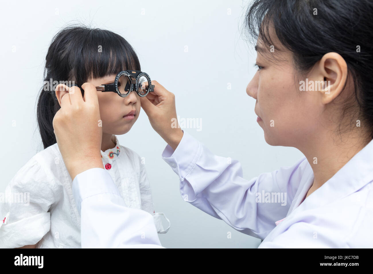 Asian Little Chinese Girl Doing Eyes Examination by ophthalmologist in isolated White Background - Stock Image