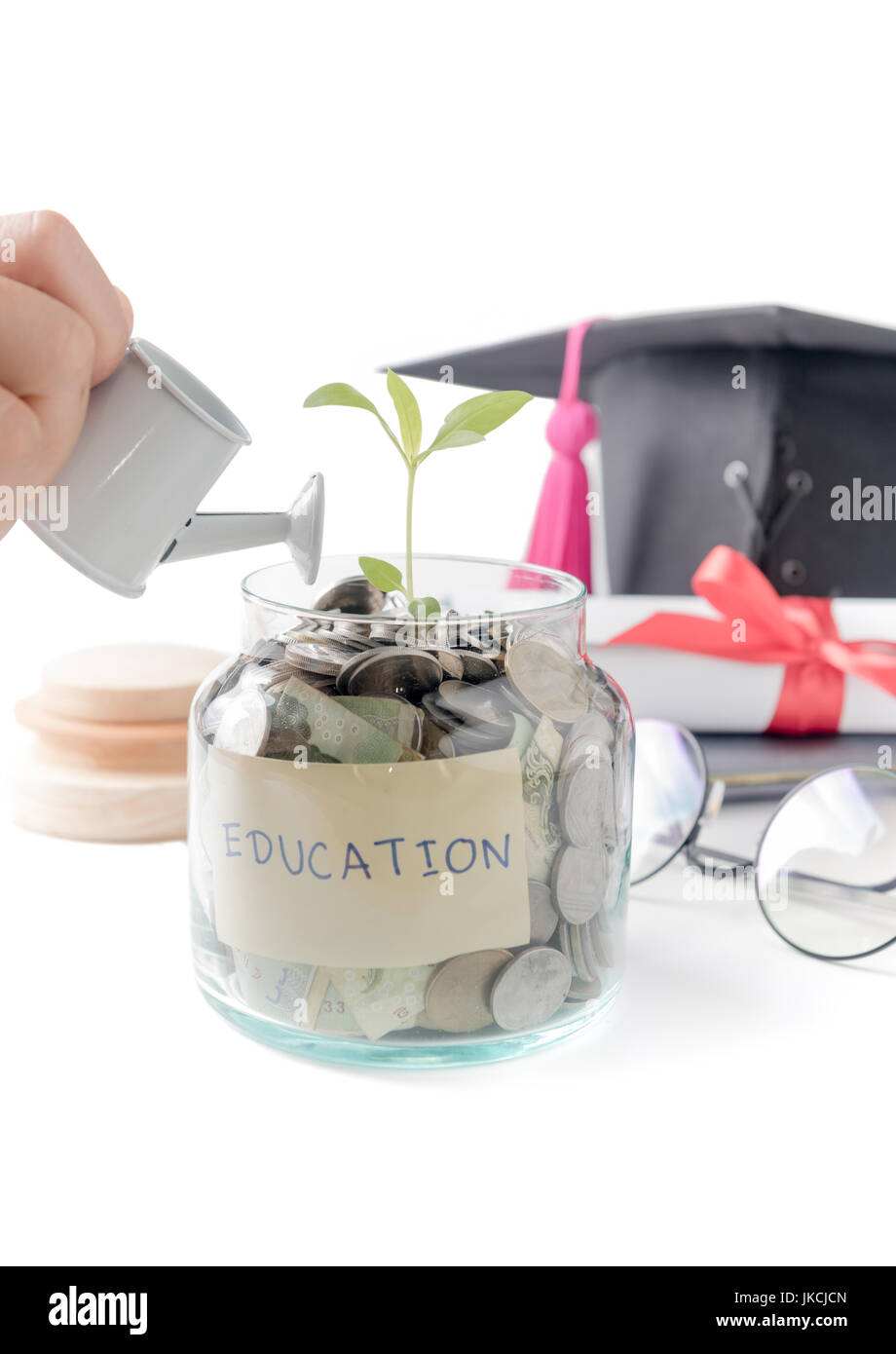 girl hand watering a tree growing out of silver coins on watering pod isolated on white background, education budget - Stock Image