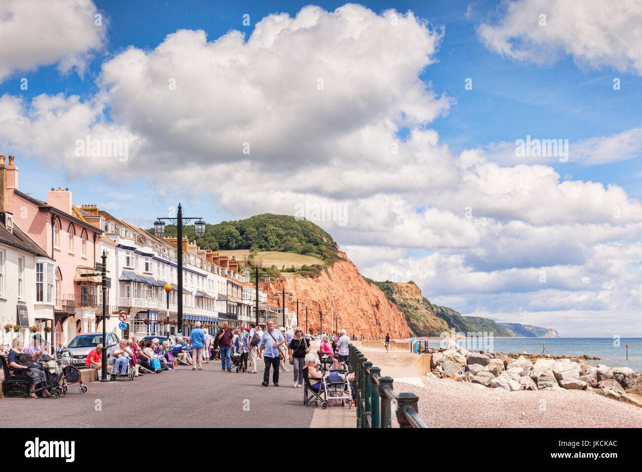 3 July 2017: Sidmouth, Dorset, England, UK - Visitors strolling on the promenade on a sunny summer day with blue Stock Photo