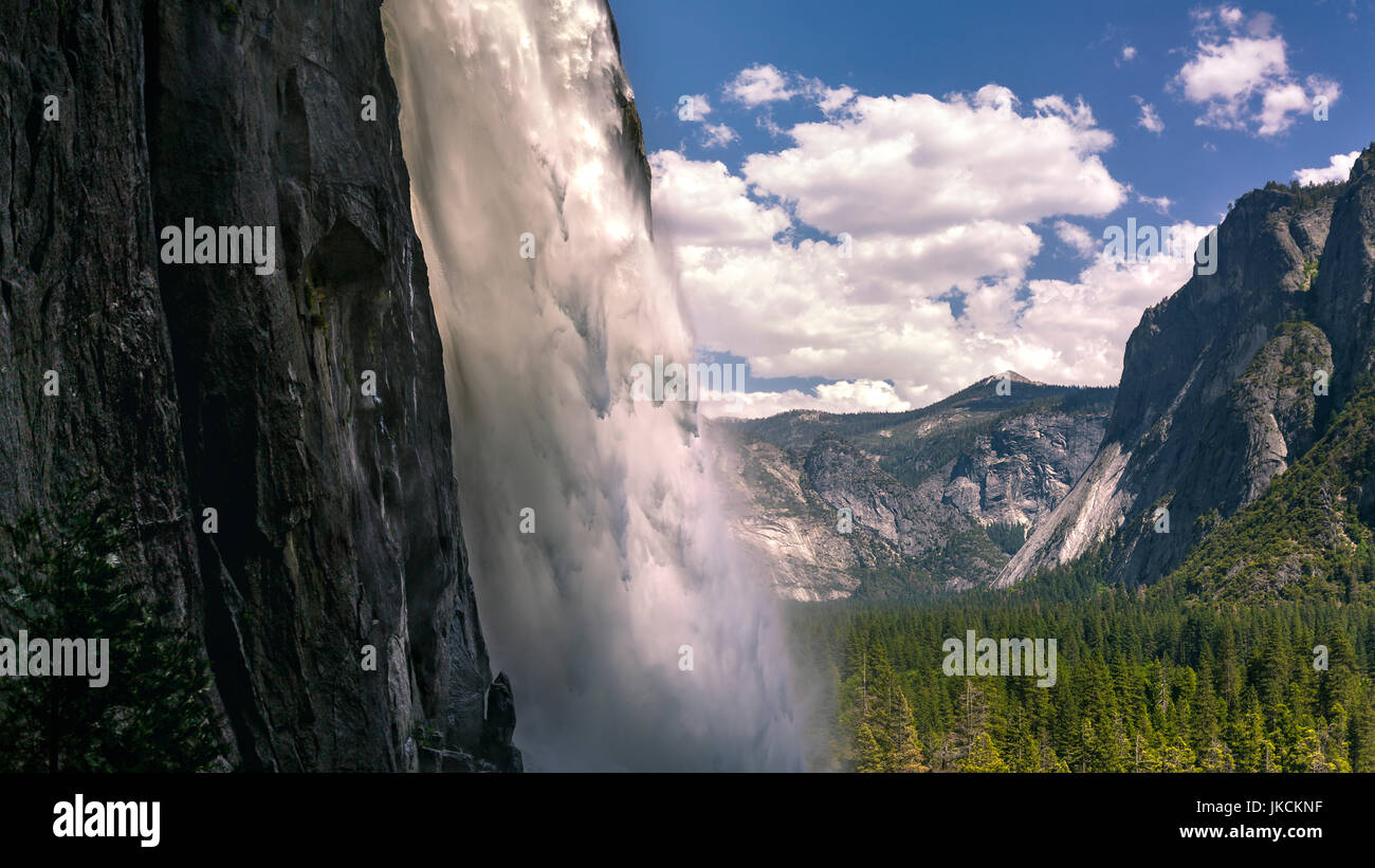 Close up of Yosemite Falls with a glowing stream and background of the valley - Stock Image