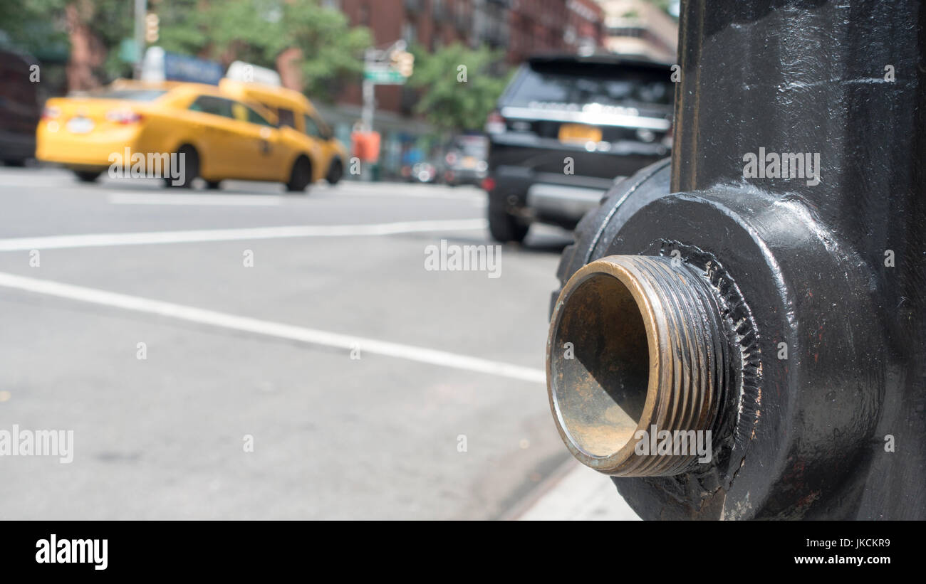 open spigot, close up, fire hydrant, low angle, blurred new york city street in motion, yellow taxi - Stock Image