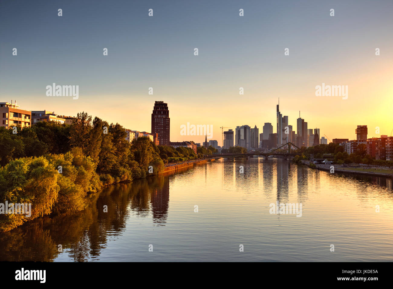 Frankfurt skyscrapers reflected on Main River and the golden hour, Germany - Stock Image