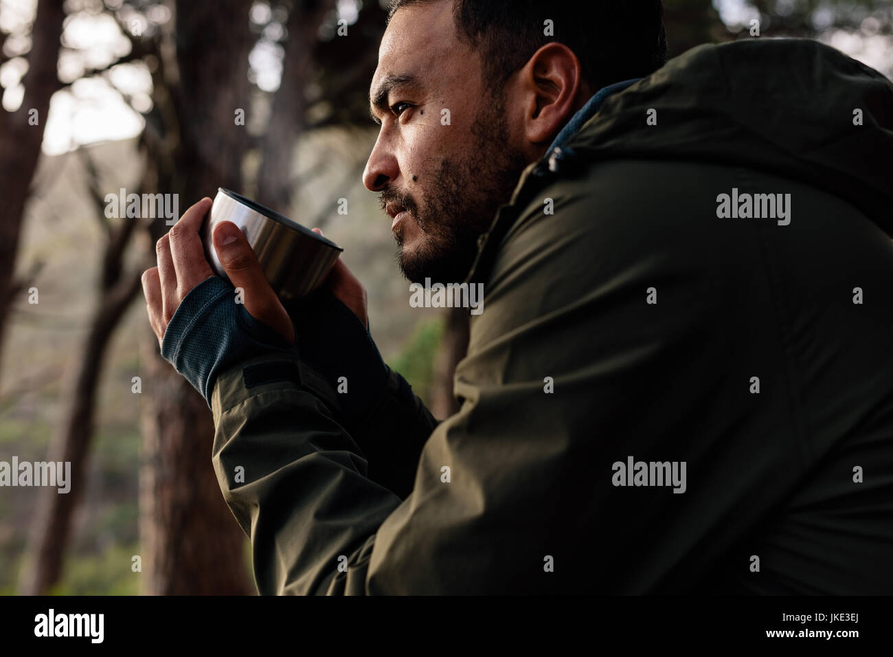 Close up shot of young man drinking hot coffee, taking break during hiking. Male hiker taking rest outdoors. - Stock Image