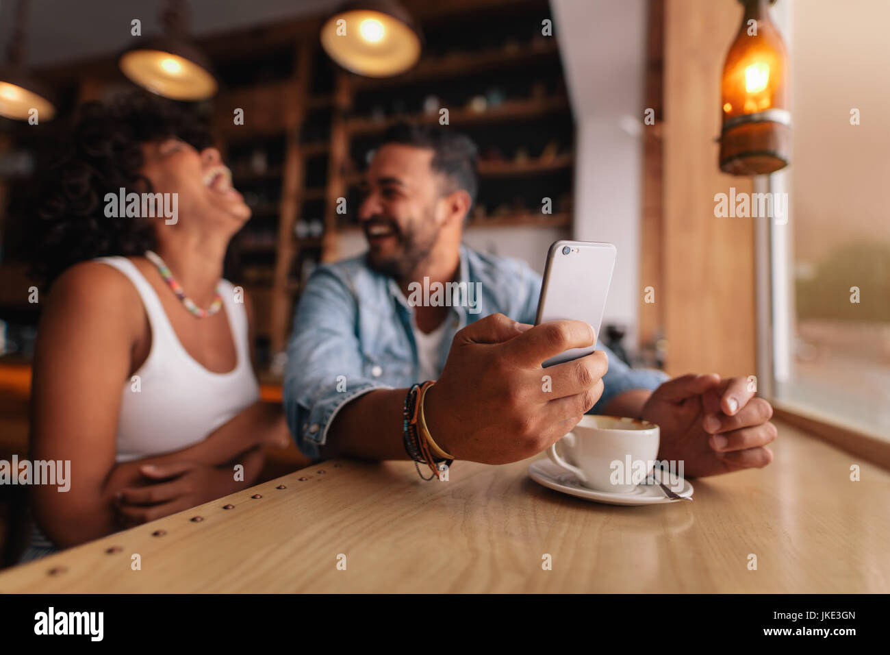 Young couple enjoying at coffee shop. Man holding mobile phone with laughing woman sitting by. - Stock Image