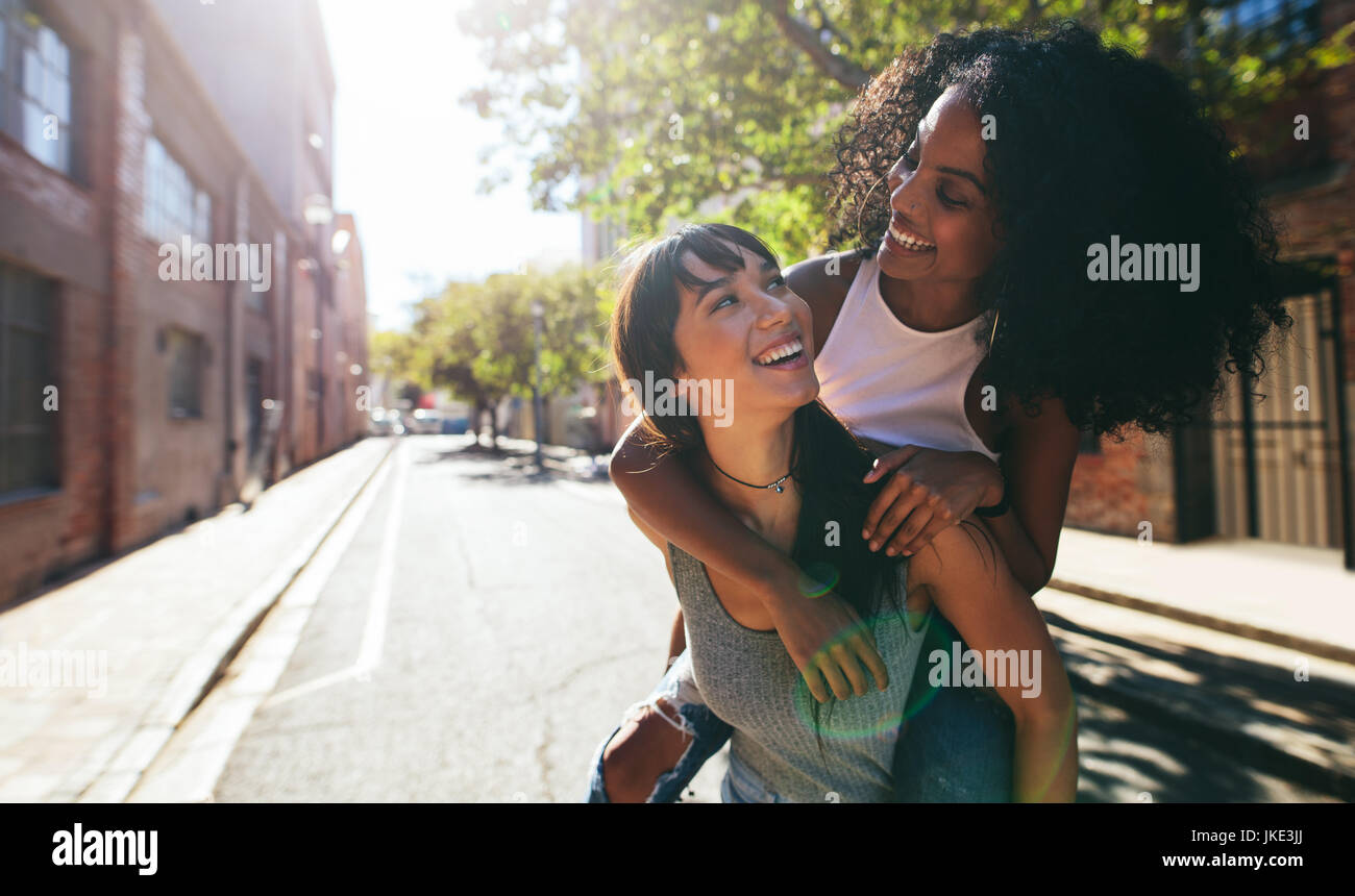 Outdoor shot of young woman carrying her female friend on her back. Two young woman having fun on city street. - Stock Image