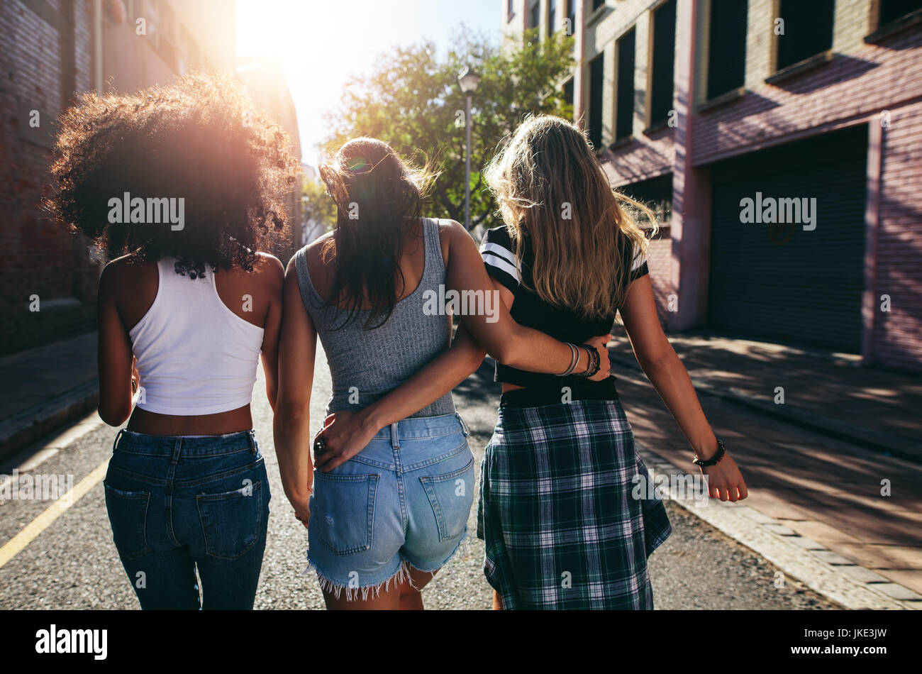 Rear view shot of three young women walking together on city street. Multiracial female friends out on the street - Stock Image
