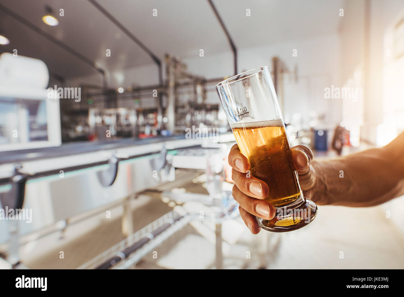 Close up of brewer testing beer at brewery factory. Man hand holding a sample glass of beer. - Stock Image