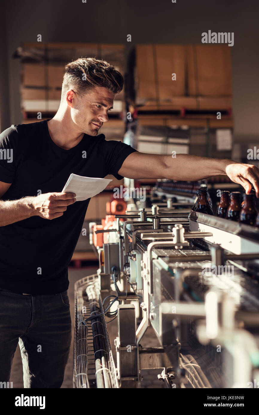Young man supervising the process of beer bottling at the manufacturing plant. Male brewer standing by conveyor - Stock Image