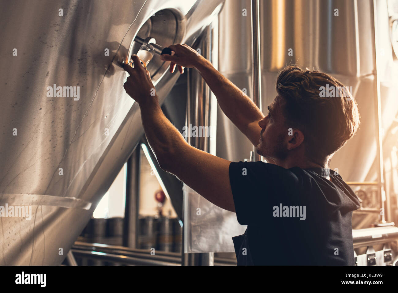 Brewer closing the hatch of brewery tank. Young male employee working in beer manufacturing factory. - Stock Image
