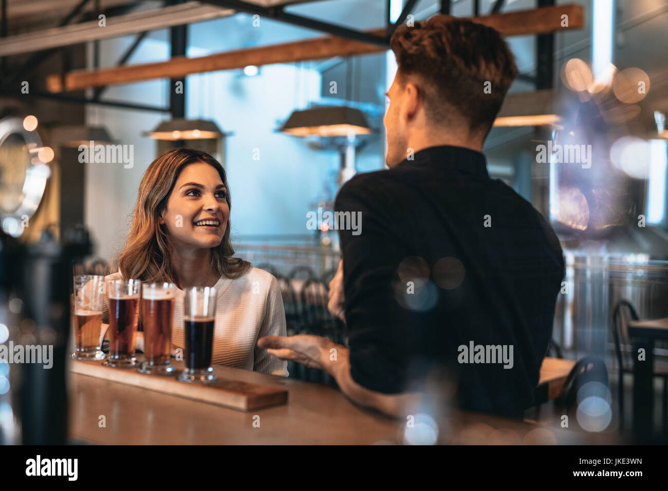 Young couple at bar with different craft beers on a wooden table. Man and woman talking at the bar counter. - Stock Image