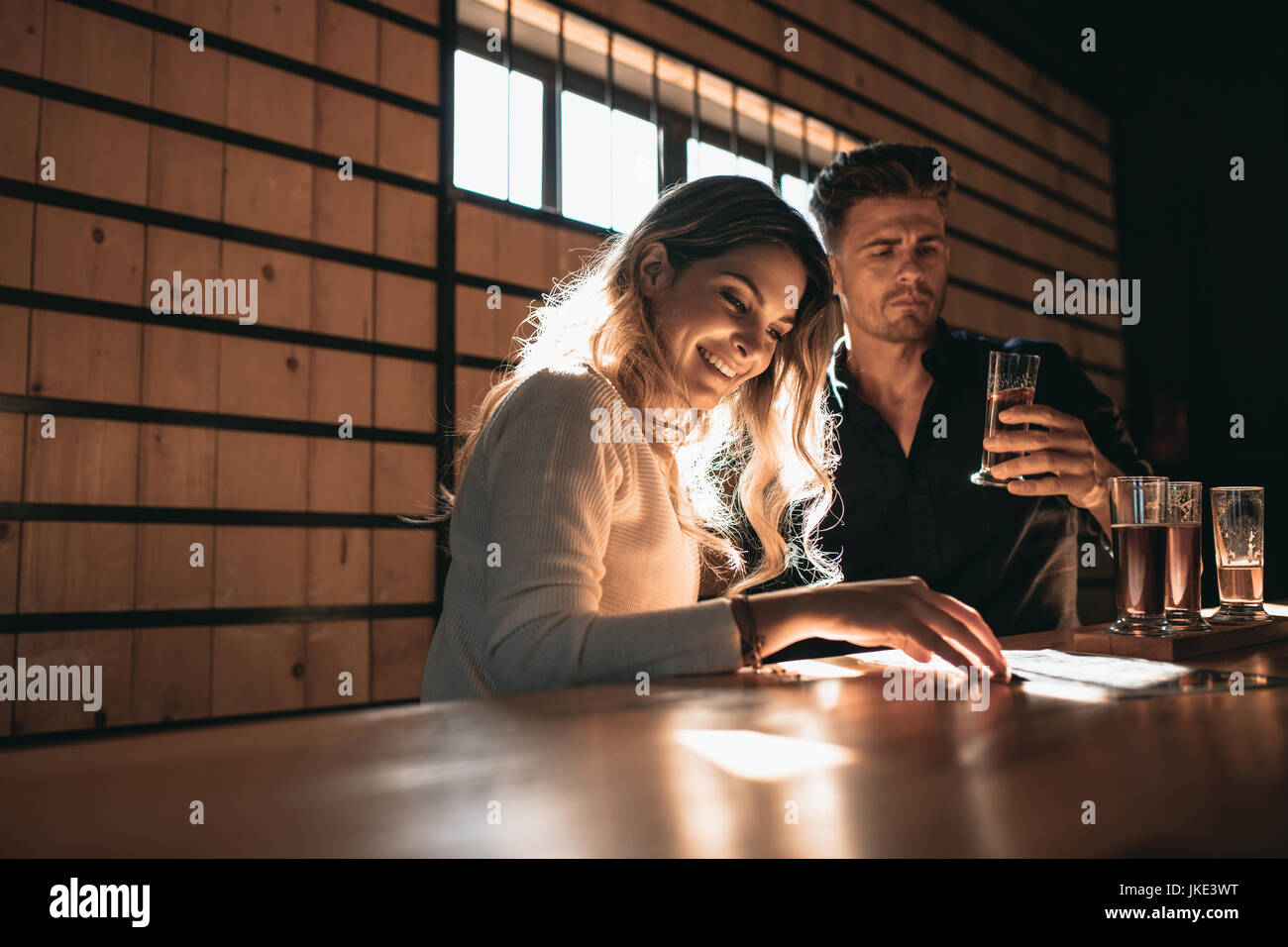 Young couple at the bar tasting different varieties of craft beers. Beautiful young woman with her boyfriend at - Stock Image