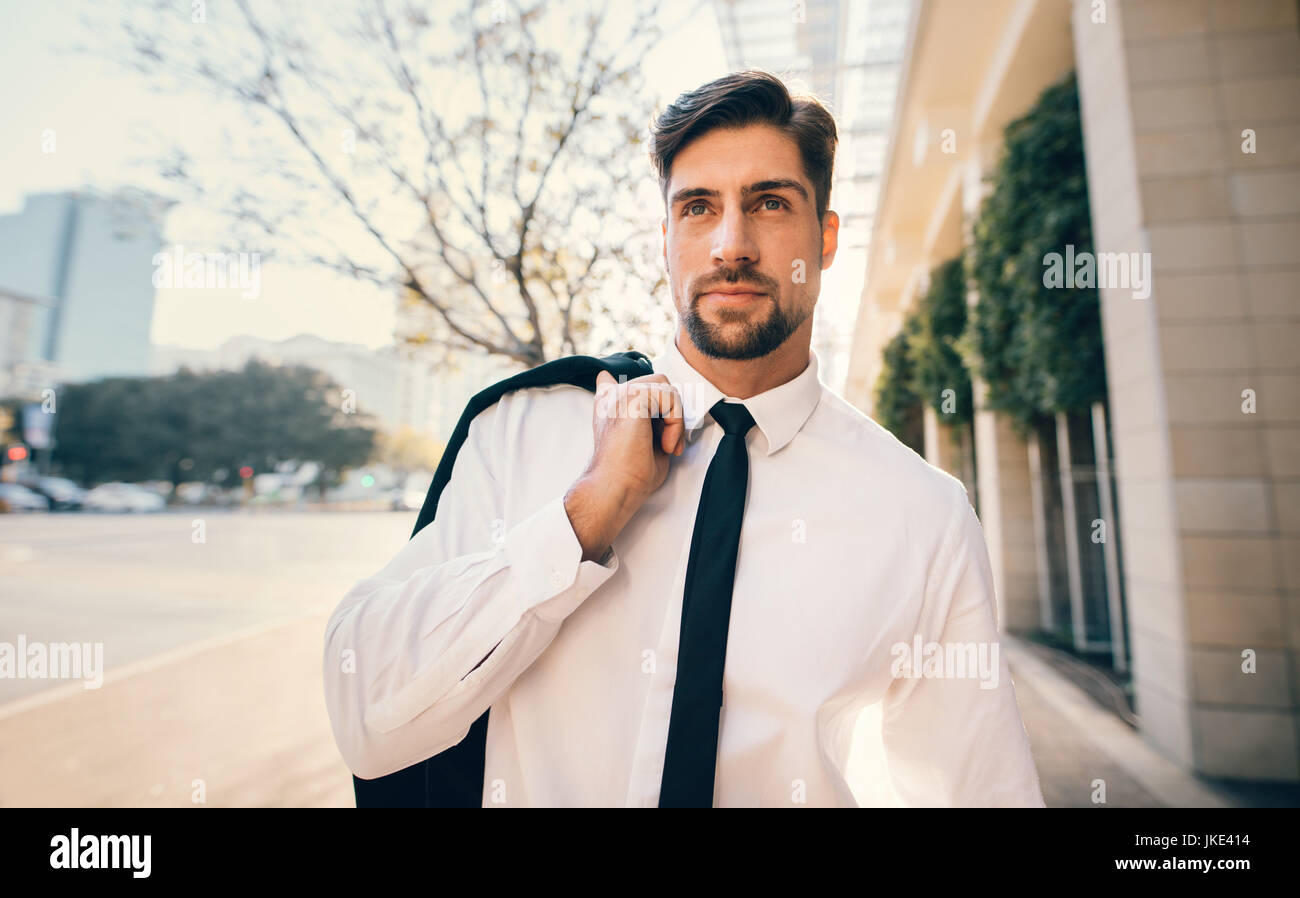 Portrait of handsome young man in formal wear walking outside on the city street. Caucasian businessman walking - Stock Image
