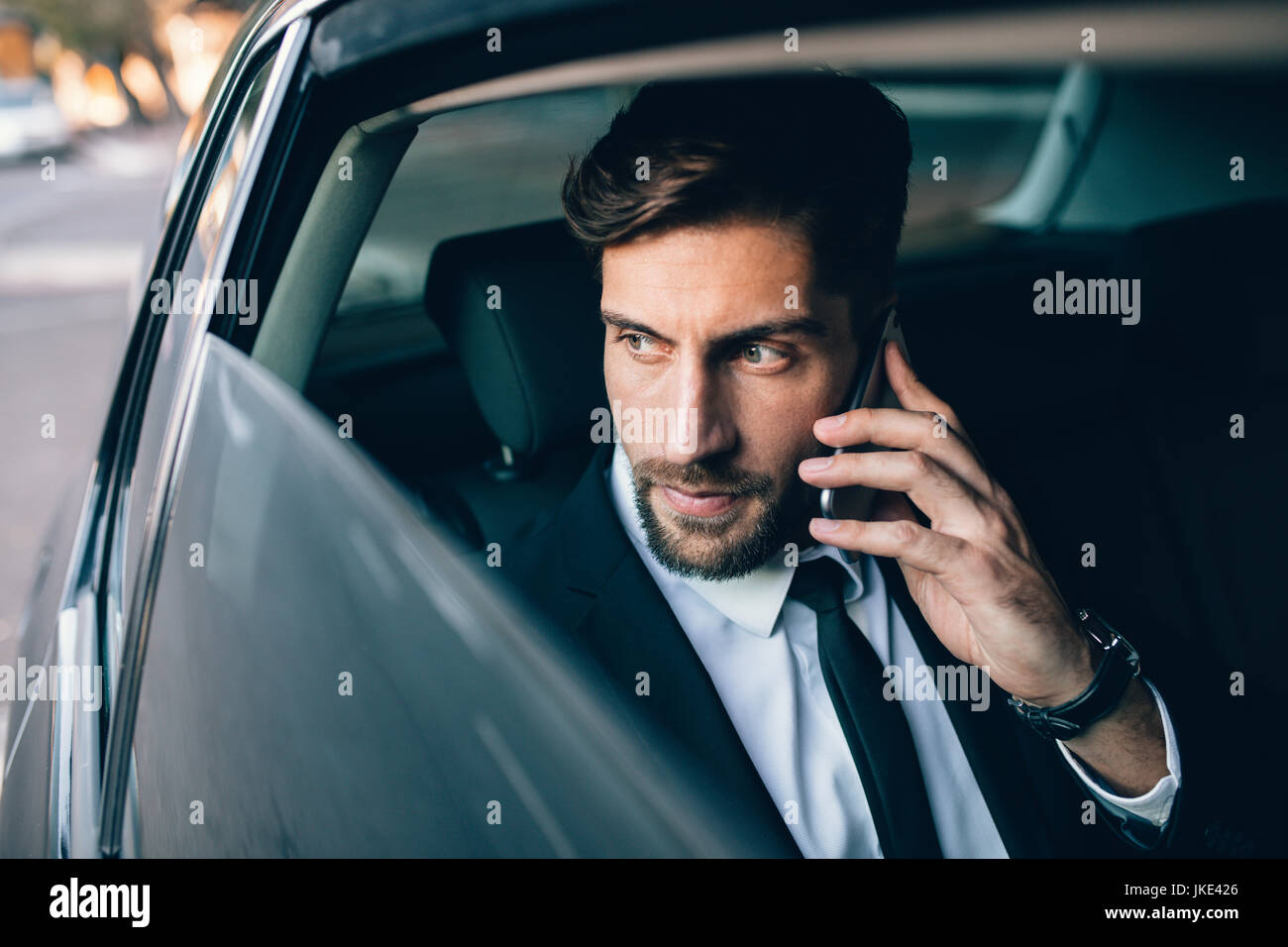Businessman talking on the mobile phone and looking outside the window while sitting on back seat of a taxi. Male - Stock Image