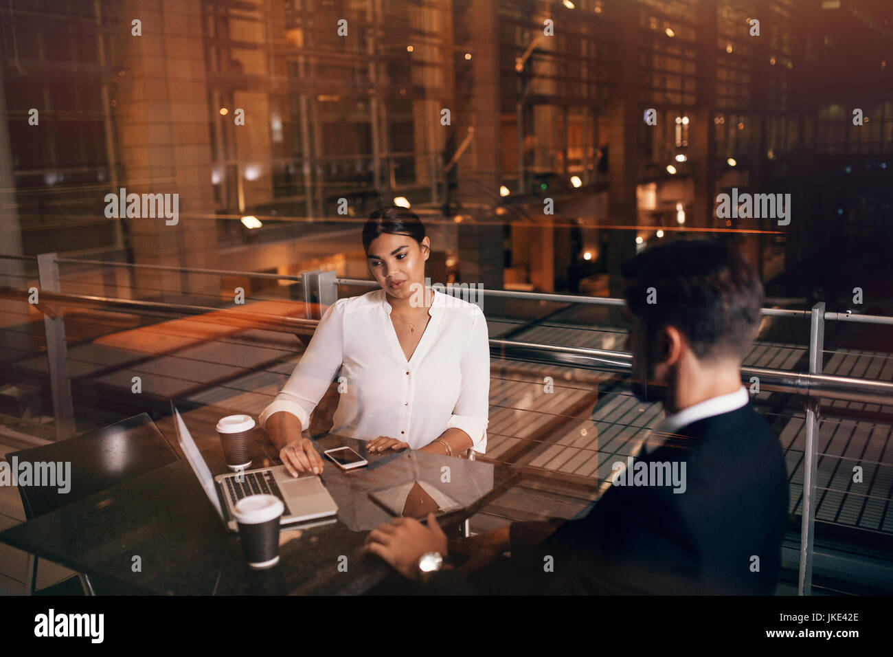 Businesswoman sitting at cafe table with man discussing business. Business people waiting at airport lounge with - Stock Image