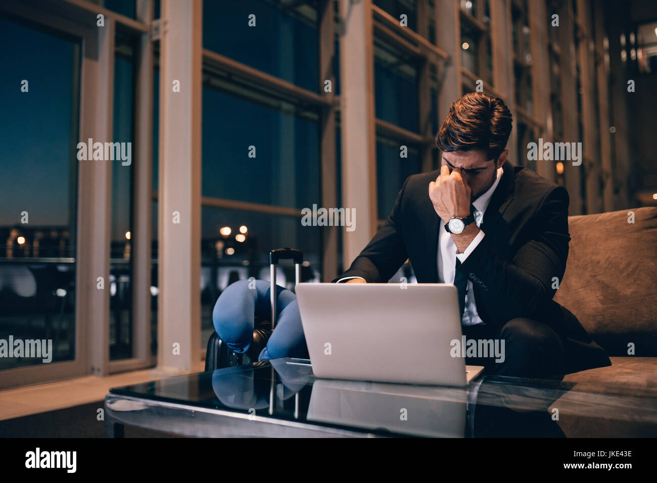 Tired businessman waiting for delayed flight in airport lounge. Young man sitting in waiting room with laptop feeling - Stock Image
