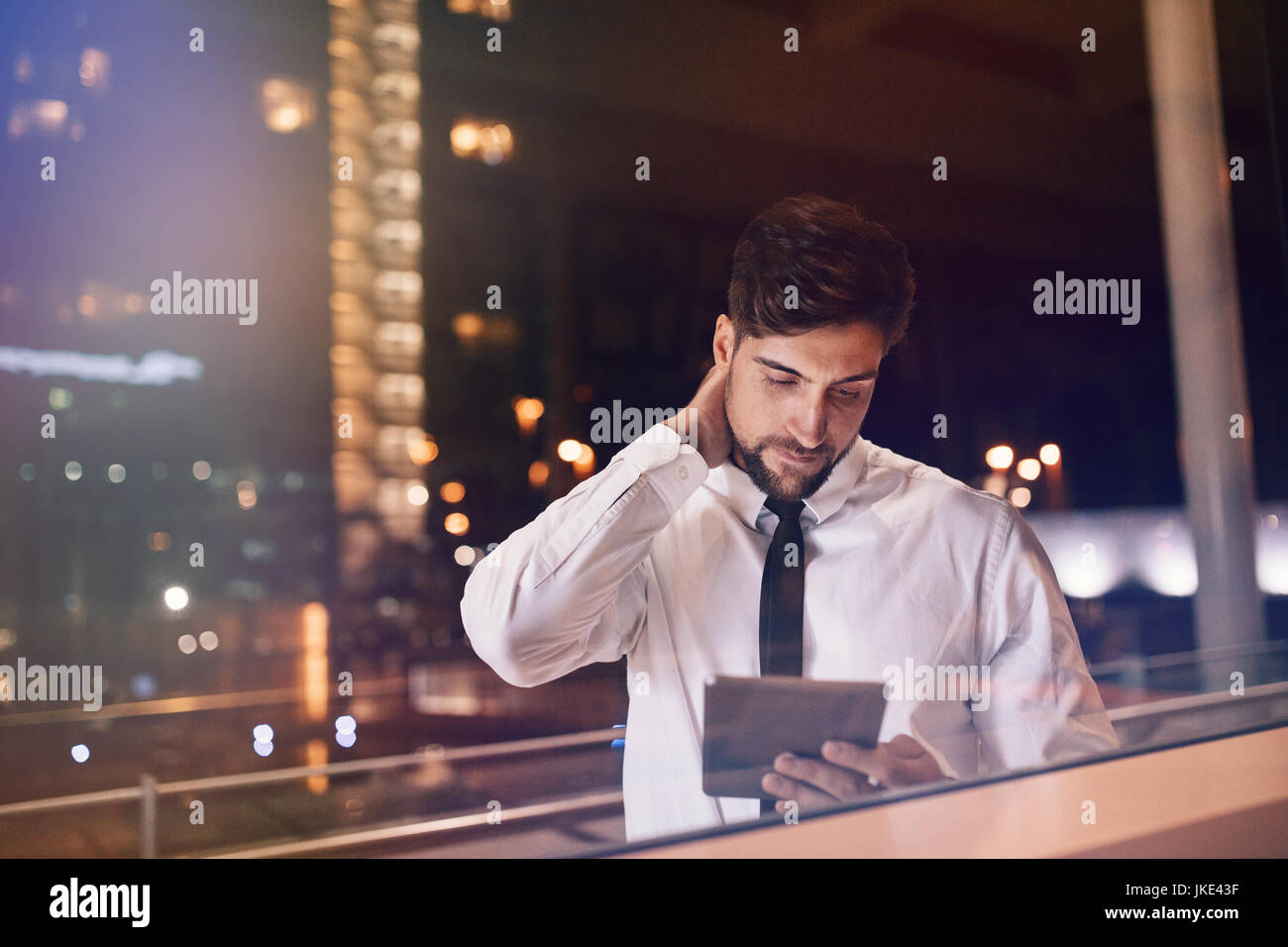 Airport lounge. Businessman inside the airport terminal using digital tablet. Handsome male executive waiting at - Stock Image