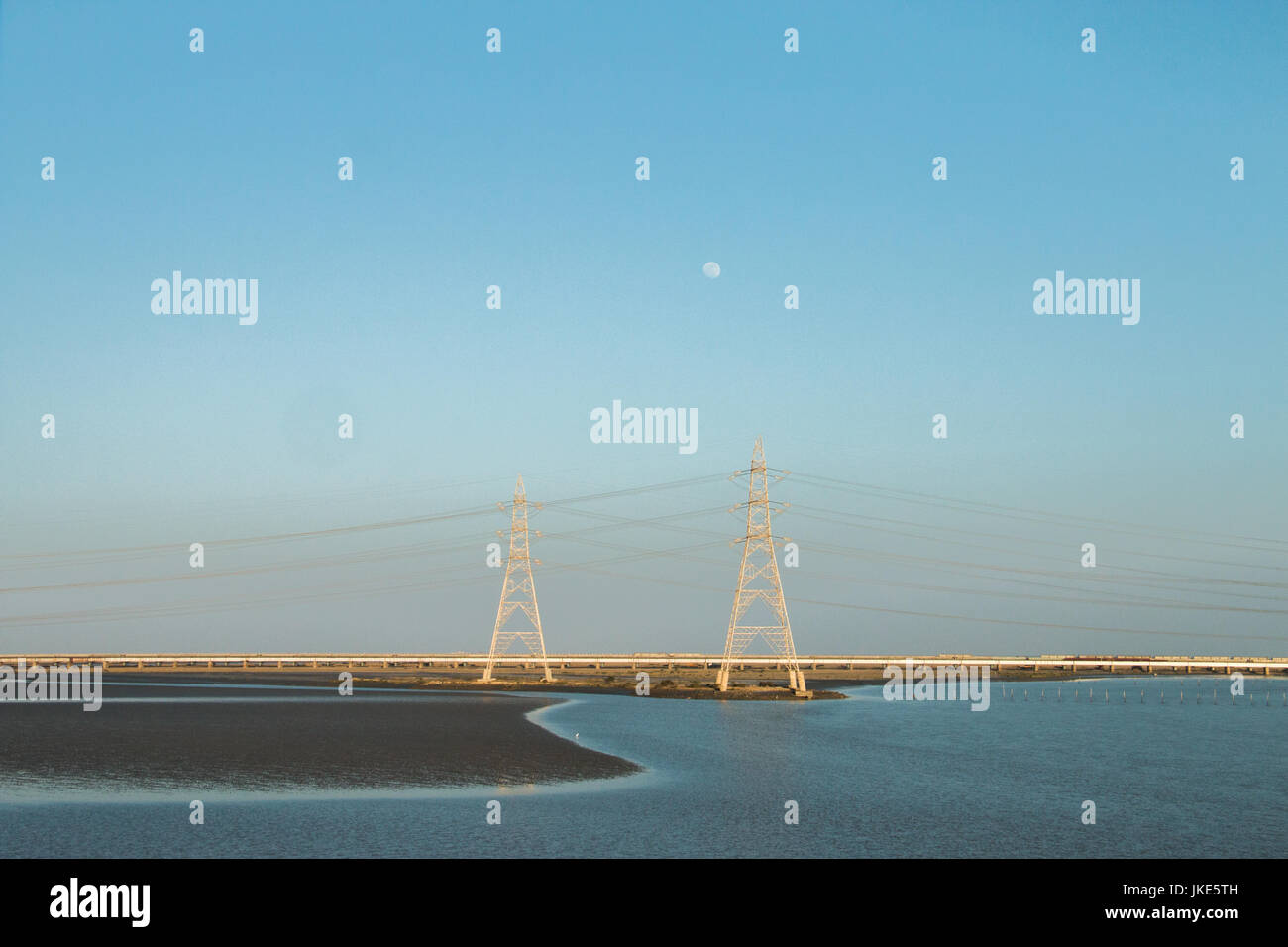 An evening on the highway , salt water area with electric poles and the moon - Stock Image
