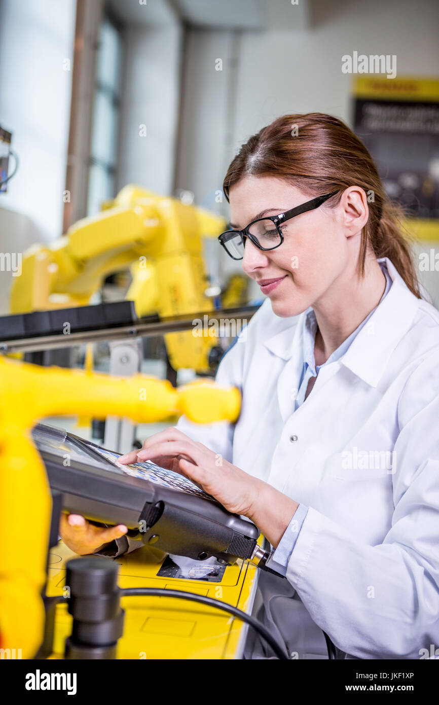 Woman using device in factory with industrial robots Stock Photo