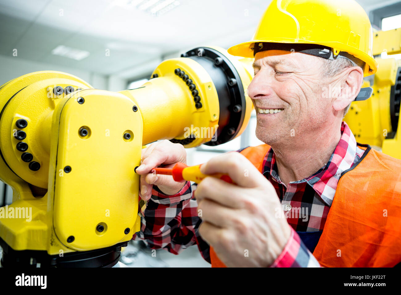 Smiling technician working on industrial robot - Stock Image