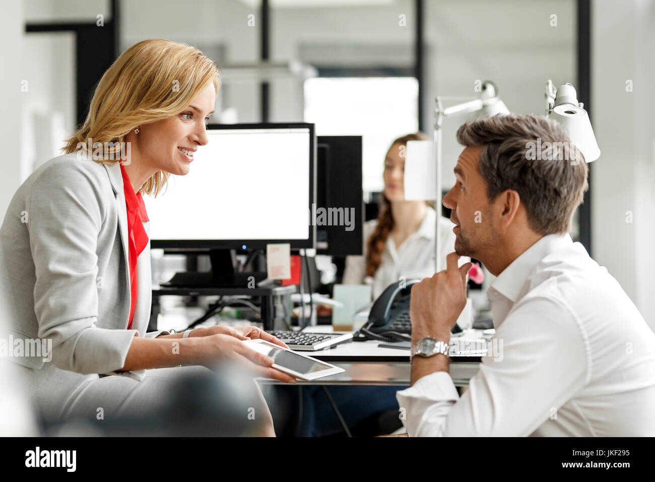 Businesswoman and businessman discussing at desk in office Stock Photo