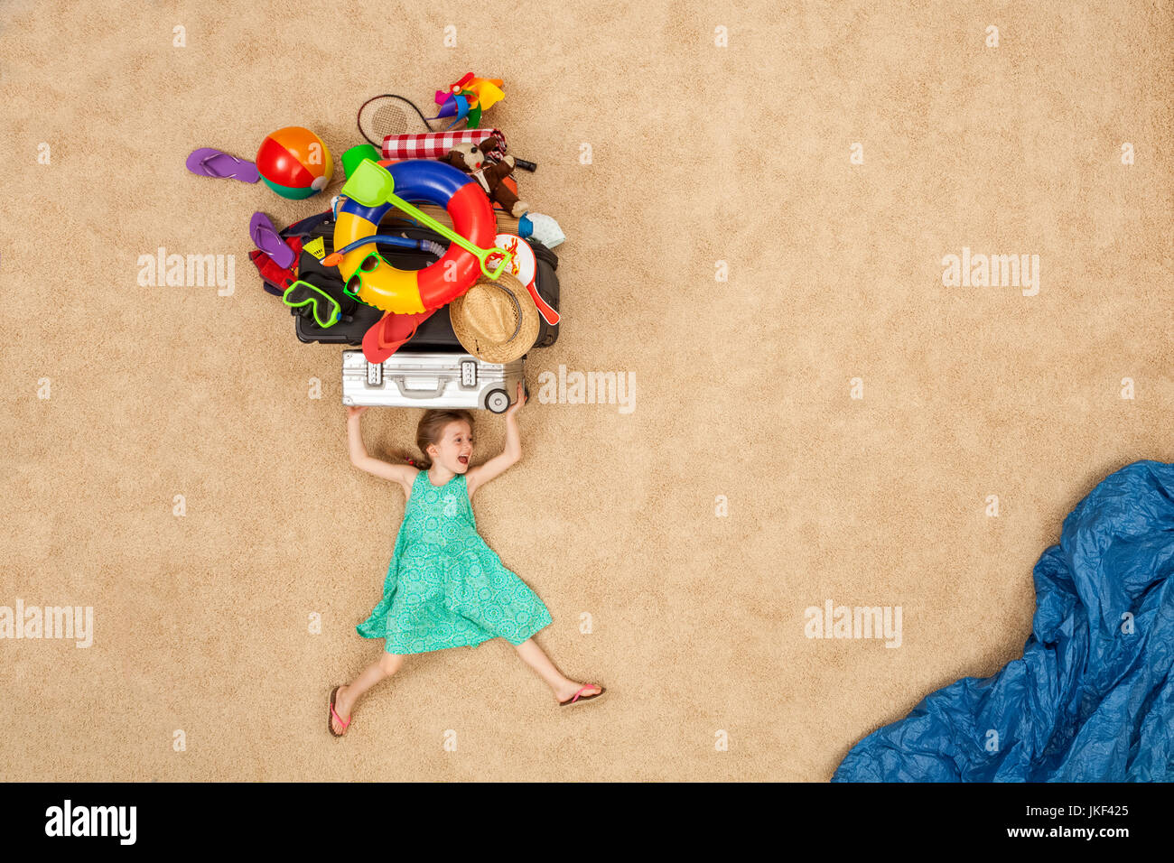 Girl running to the sea, carrying beach equipment on the head - Stock Image