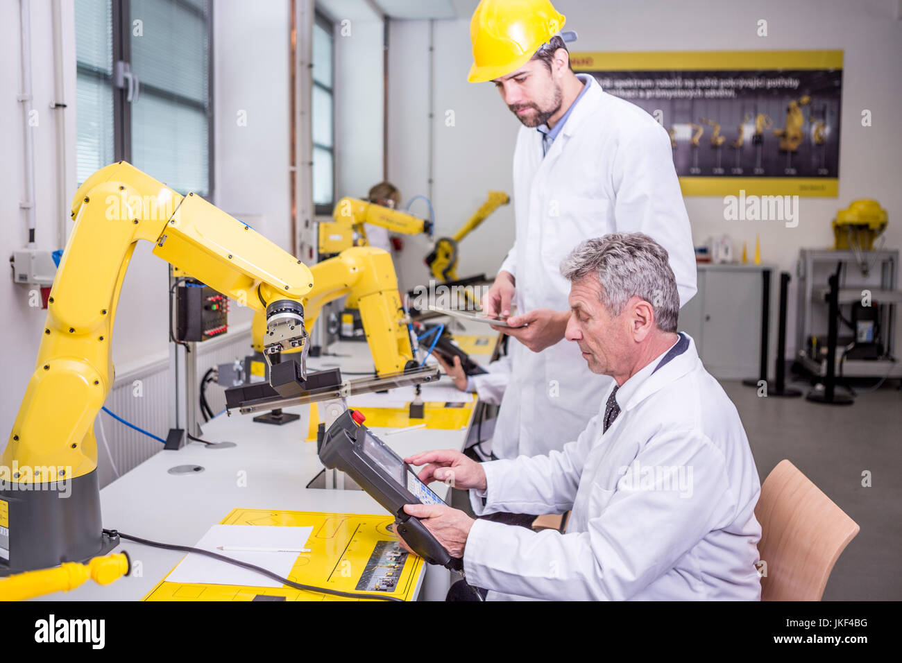 Two engineers in factory looking at device - Stock Image
