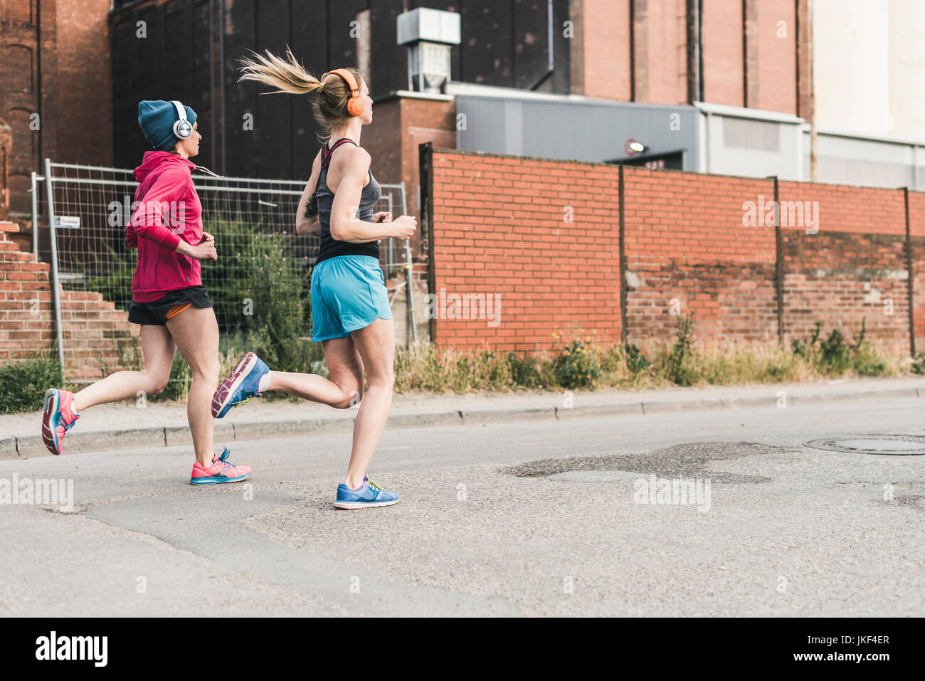 Two women running on the street along factory building - Stock Image