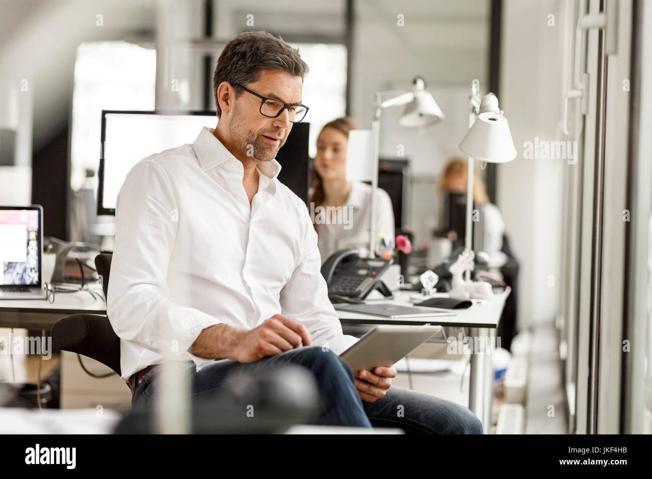Businessman at desk in office using tablet - Stock Image