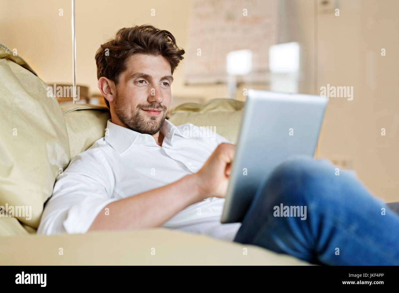 Smiling man in office using tablet in bean bag - Stock Image