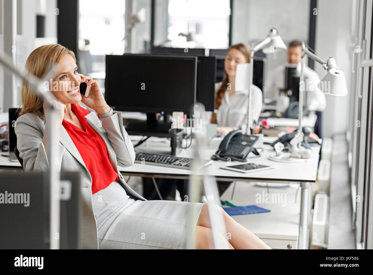 Businesswoman at desk in office on cell phone - Stock Image