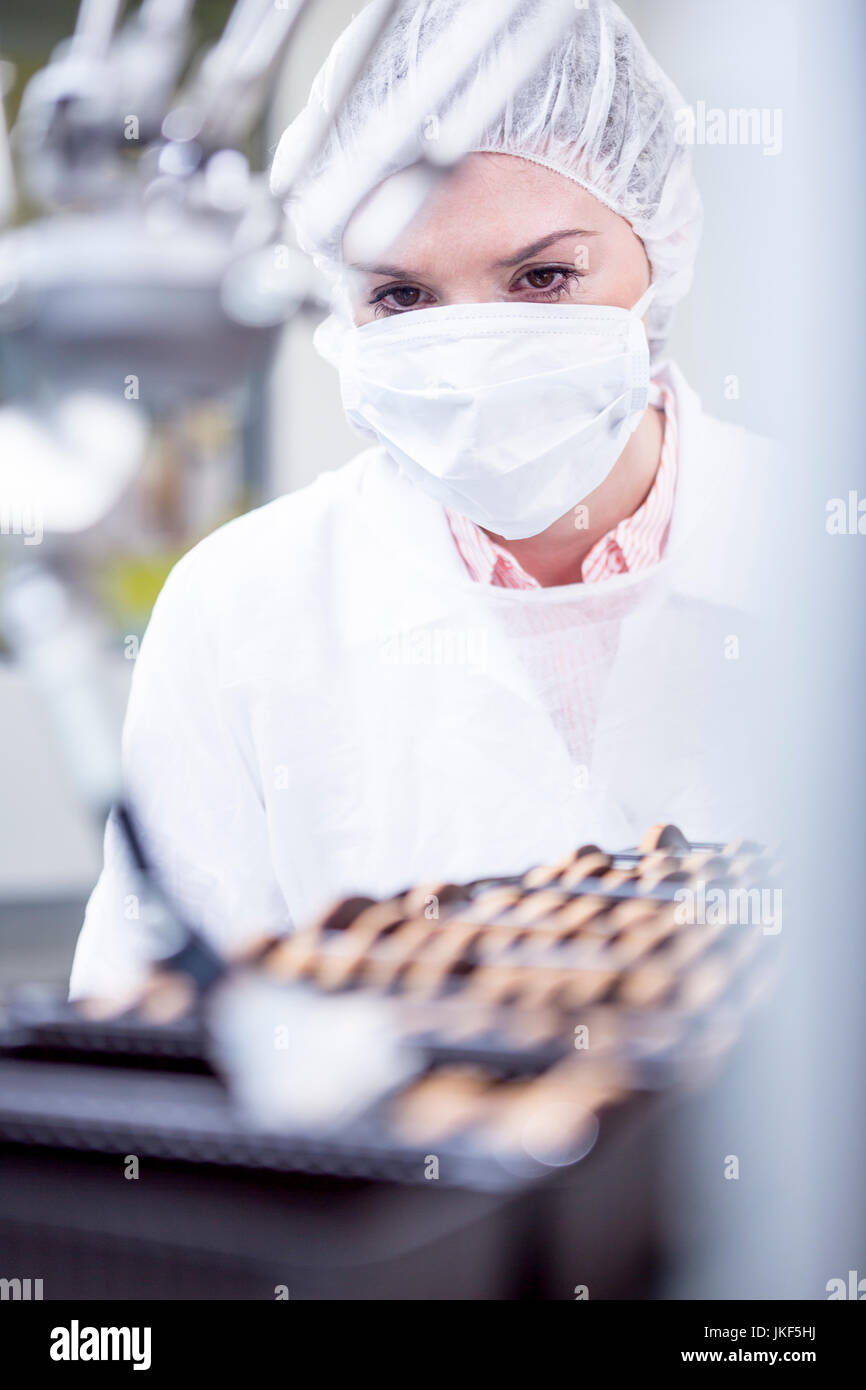 Woman in factory looking at robot handling cookies Stock Photo