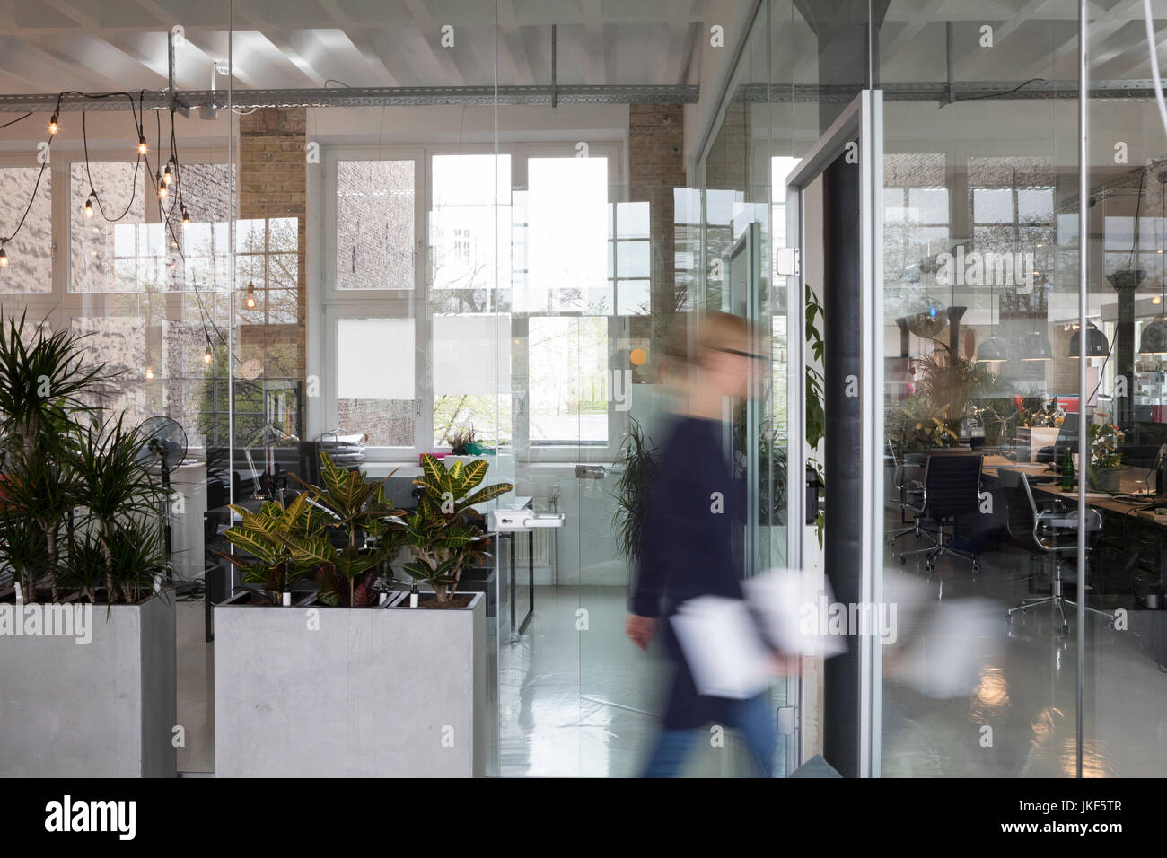 Blurred motion of a businesswoman moving in office - Stock Image