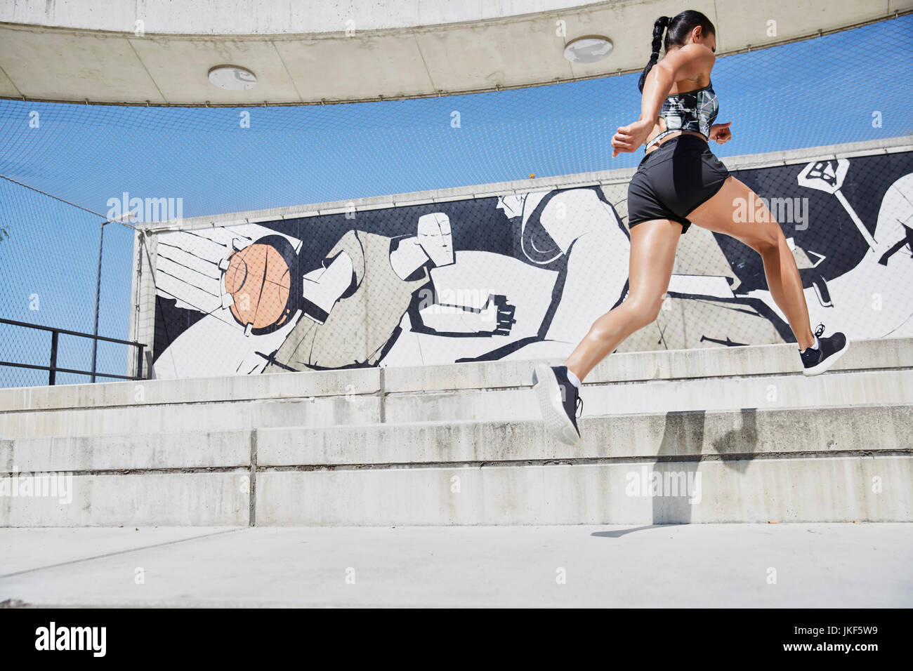 Fit woman running outdoors - Stock Image
