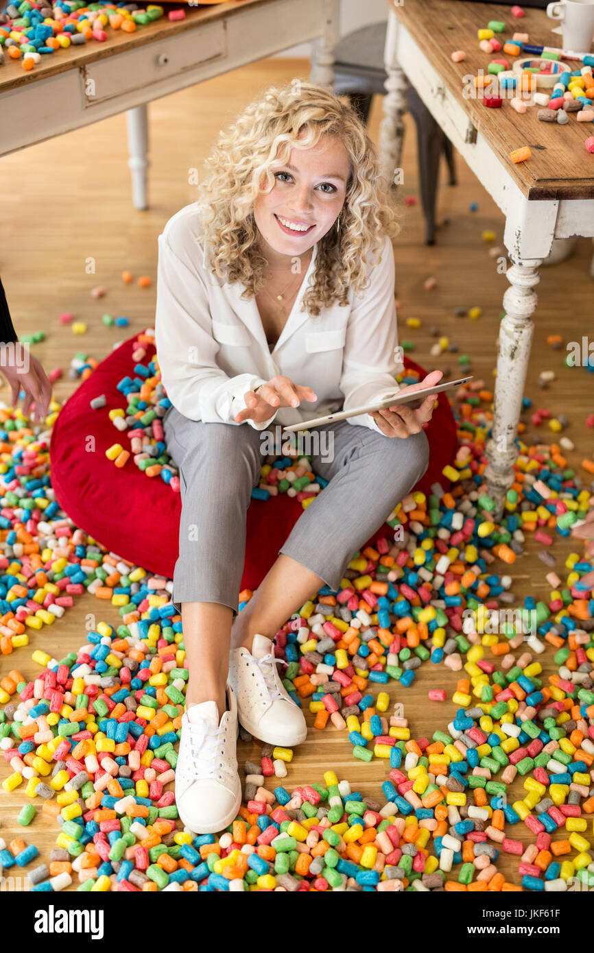 Woman using tablet in office surrounded by colorful polystyrene parts - Stock Image