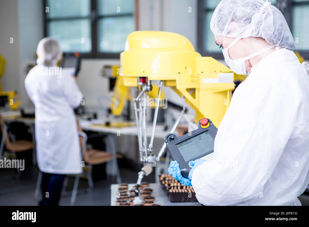 Woman in factory examining robot handling cookies Stock Photo
