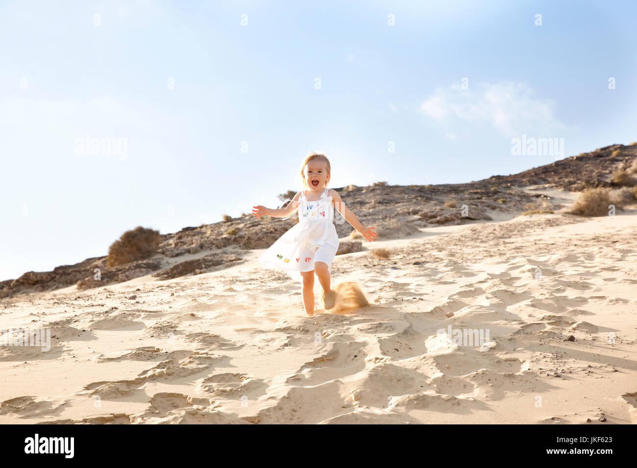 Spain, Fuerteventura, girl running down dune on the beach - Stock Image