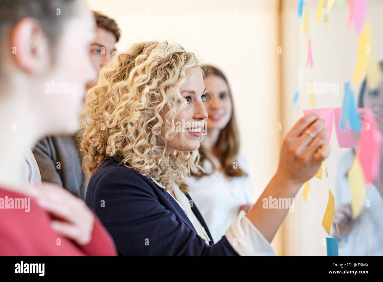 Colleagues in office at glass pane with adhesive notes - Stock Image