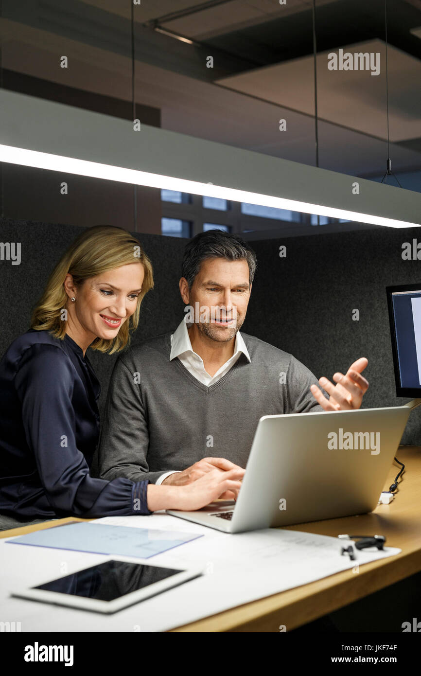 Businesswoman and businessman with laptop in meeting box Stock Photo