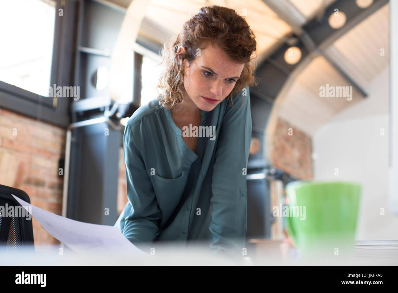 Young woman working at desk in modern office - Stock Image