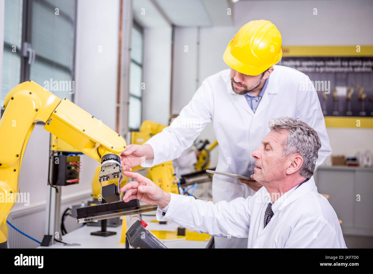 Two engineers examining industrial robot - Stock Image