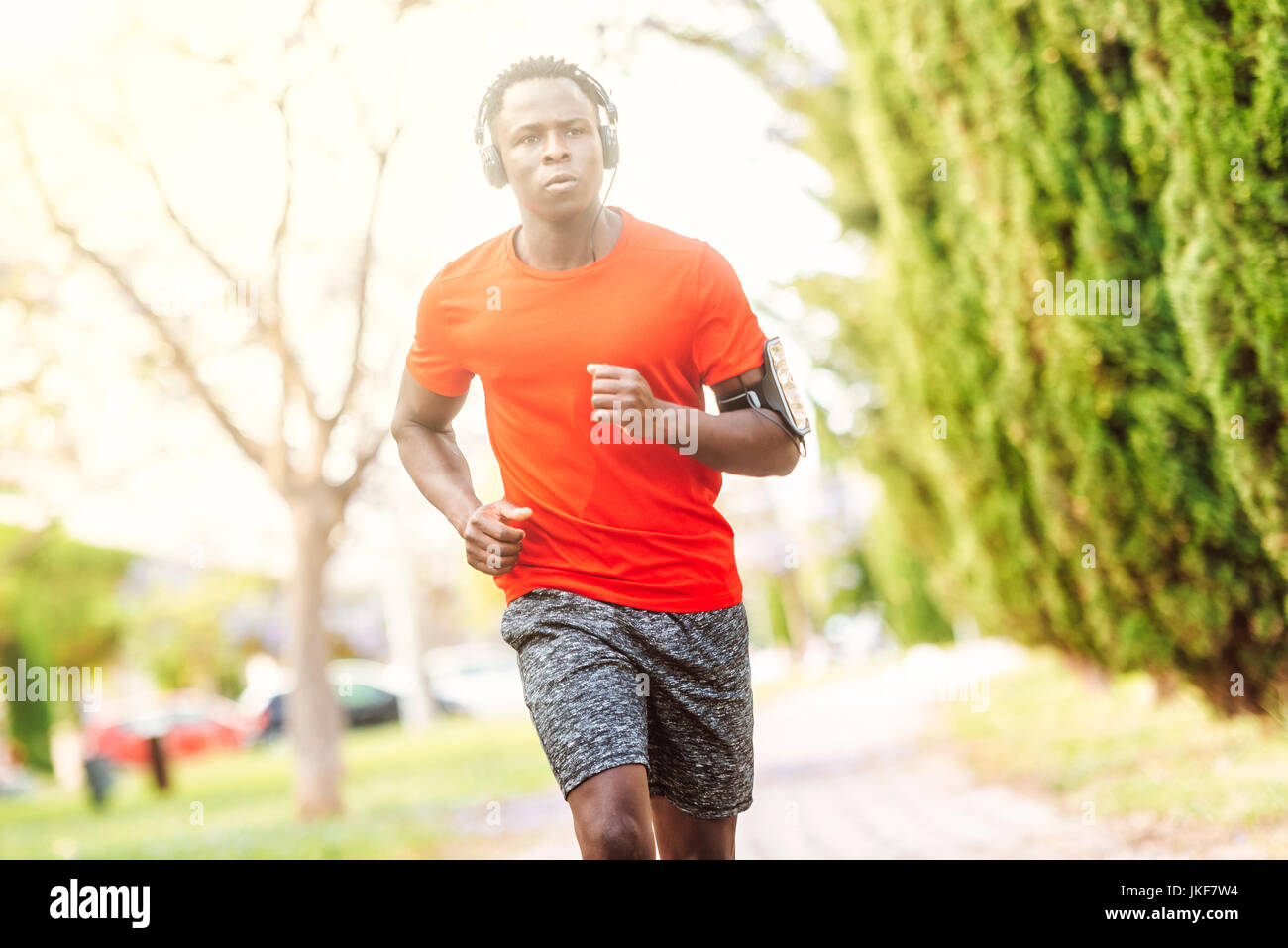 Portrait of man in sportswear running through a park listening music with headphones - Stock Image