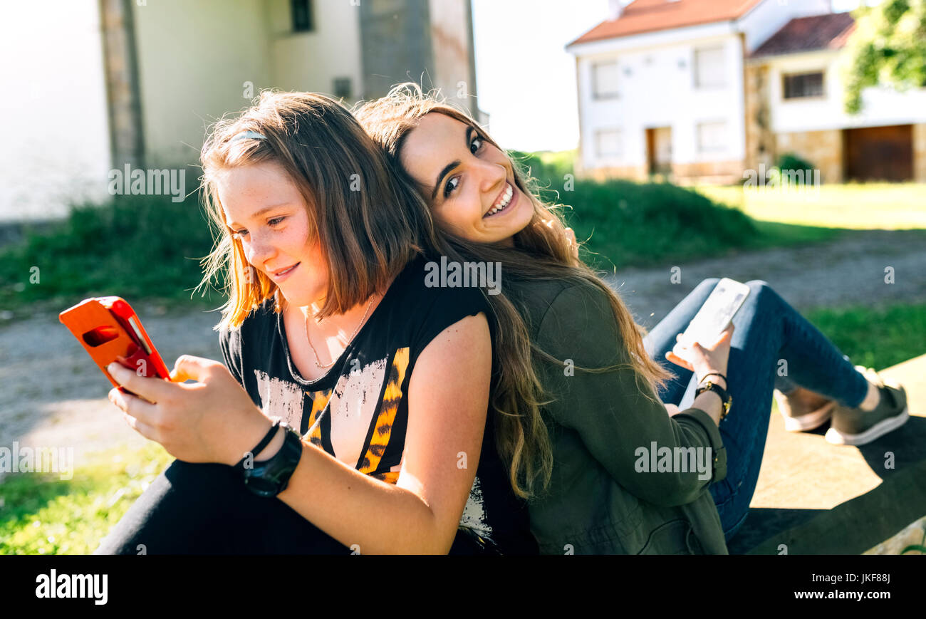 Two happy girls using their smartphones outdoors Stock Photo