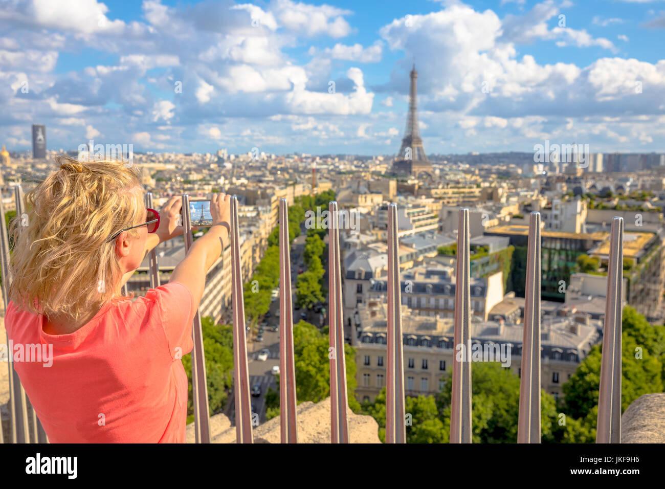 Woman photographs Eiffel Tower Stock Photo