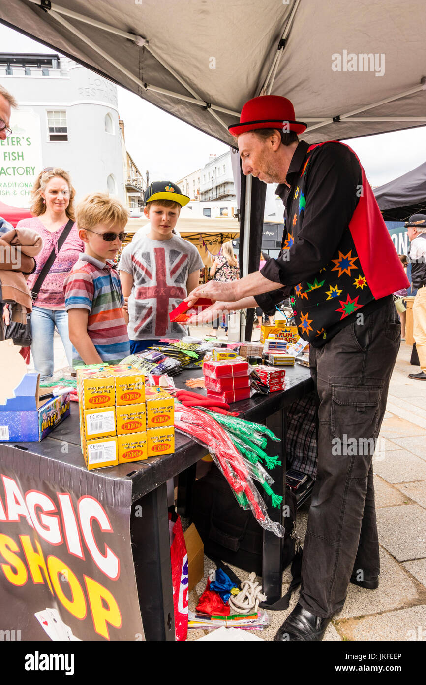 Open market stall with magic tricks on. Zenea, local magician, demonstrates to family with two children, how some - Stock Image