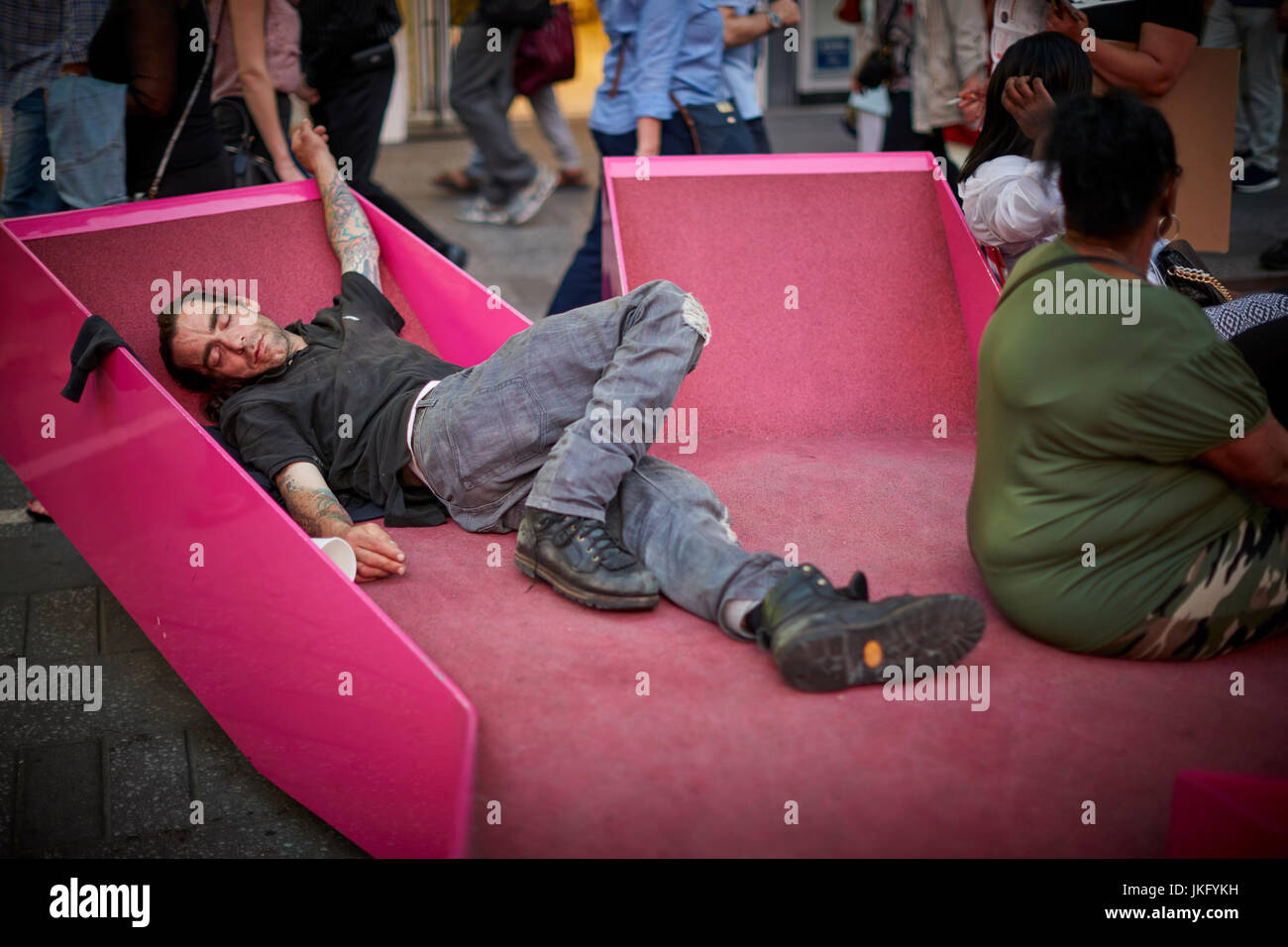 New York City, Manhattan, United States, man sleeping amongst the tourists on modern pink street furniture benches - Stock Image