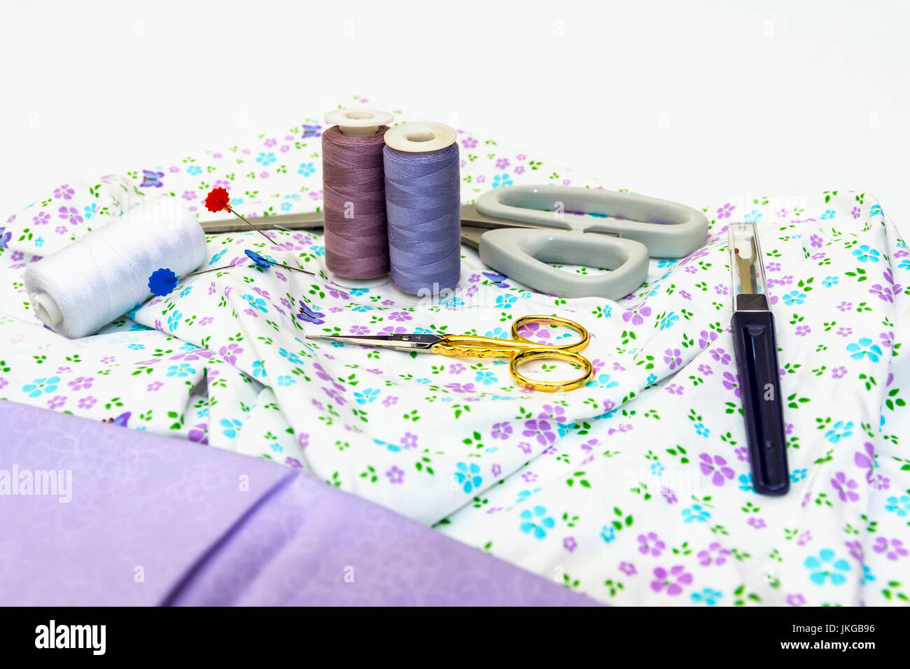 A selection of Sewing Accessories, including Scissors, Cotton, with Plain and Pattern Fabric displayed on white background. Stock Photo