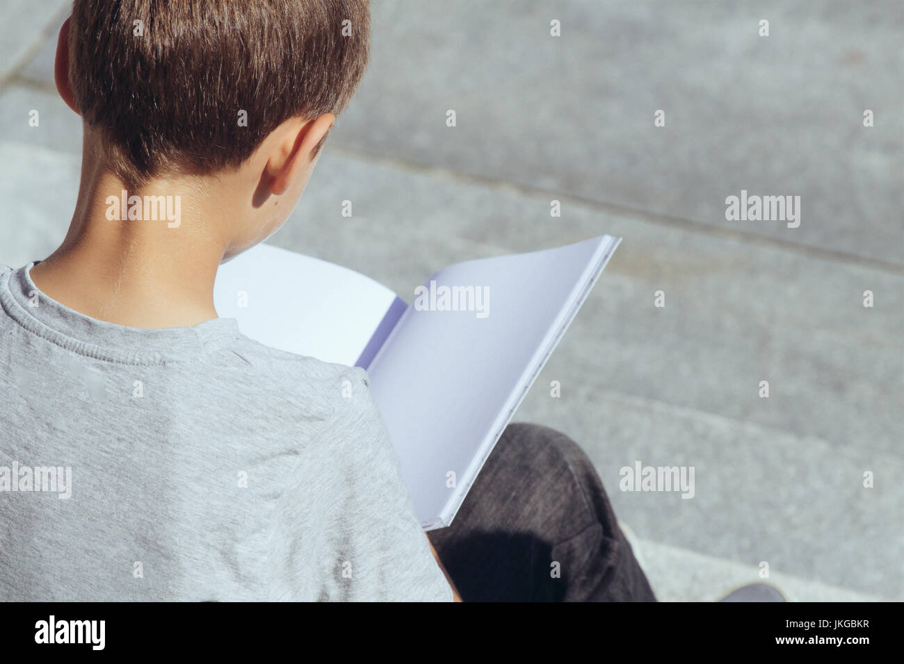 Young boy reading book outdoors - Stock Image