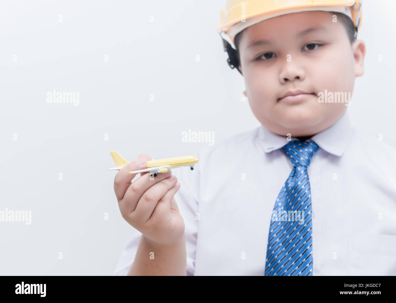 airplane in hand young engineer pilot on white background, children's dream career concept - Stock Image