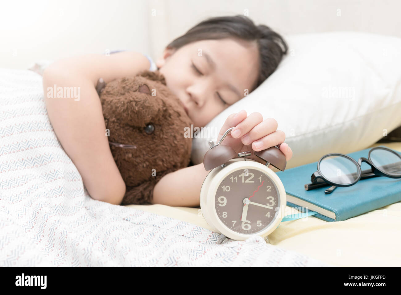 cute little hand girl reaching to turn off alarm clock on the bed in the morning - Stock Image